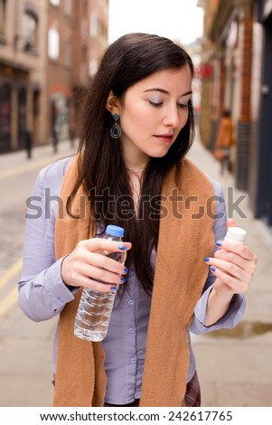 young woman holding her pills and a bottle of water in the street - stock photo
