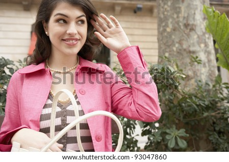 Young woman holding her purse in a shopping street. - stock photo