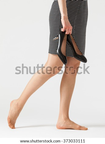Young woman holding her shoes, white background - stock photo