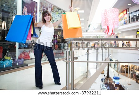 young woman holding in hands multi-coloured bags with purchases