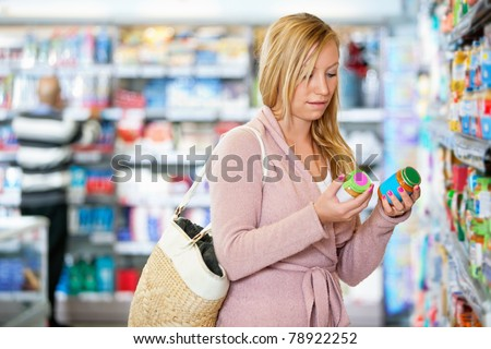 Young woman holding jar in the supermarket with people in the background - stock photo