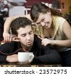 Young woman holding jumper cables coming out of coffee mug to man's head - stock photo