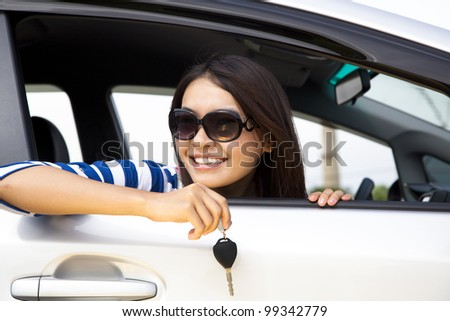 young woman holding key in car - stock photo