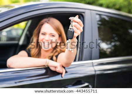 Young woman holding keys to new car - stock photo