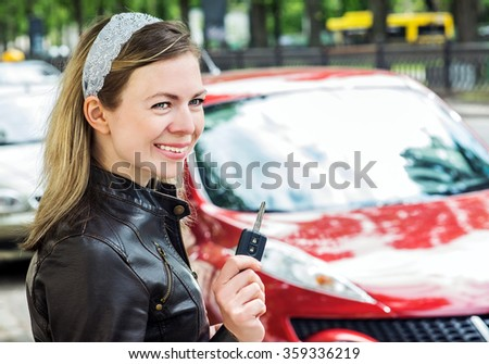 Young woman holding keys to new car and smiling - stock photo