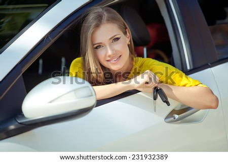 Young woman holding keys to new car and smiling at camera - stock photo