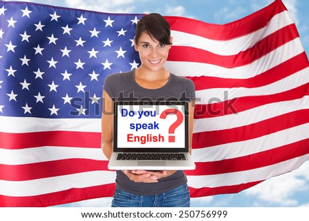 Young Woman Holding Laptop Asking Do You Speak English In Front Of Usa Flag - stock photo