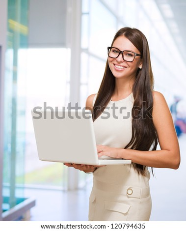 Young Woman Holding Laptop in a building - stock photo
