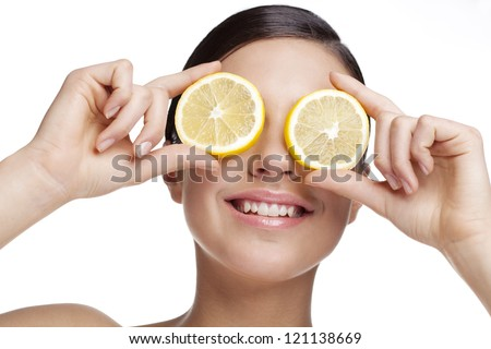 young woman holding lemon slice in front of eye. All skin detail has been kept, no filters used - stock photo