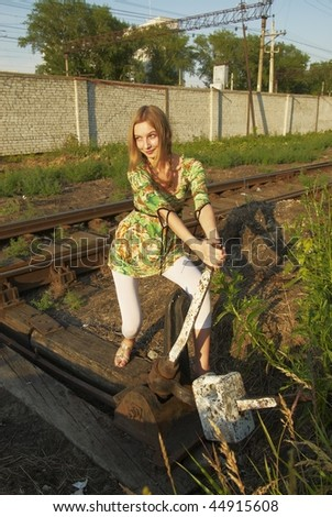 Young woman holding lever of old manual switcher of railway direction