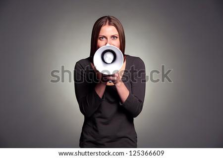 young woman holding loudspeaker. studio shot over dark background - stock photo