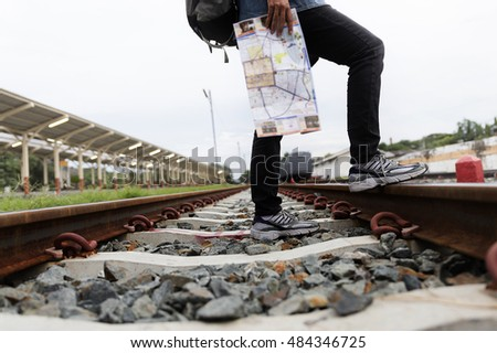 young woman holding map with backpack standing on railway at train station - travel concept
