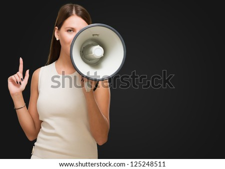 Young Woman Holding Megaphone against a black background - stock photo