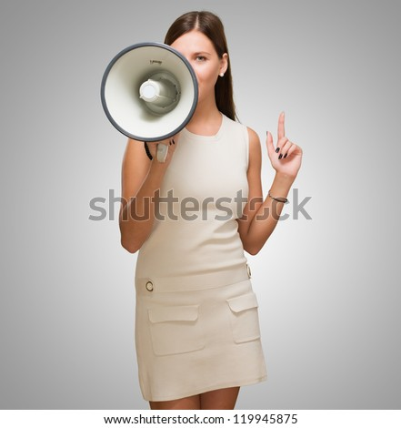 Young Woman Holding Megaphone against a grey background - stock photo