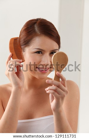 Young woman holding mirror and wooden comb