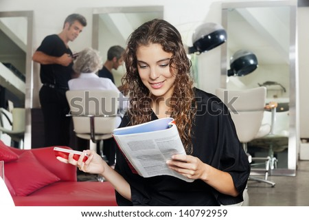 Young woman holding mobile phone while reading magazine with hairdresser and senior woman in the background at hair salon