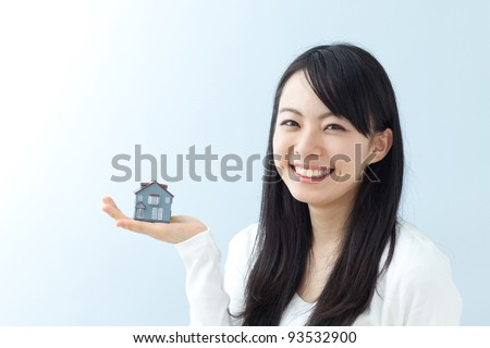 young woman holding model house - stock photo
