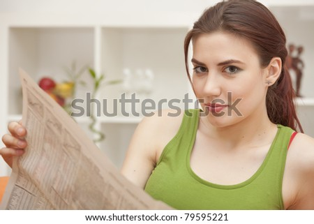 young woman holding newspaper sitting on sofa - stock photo