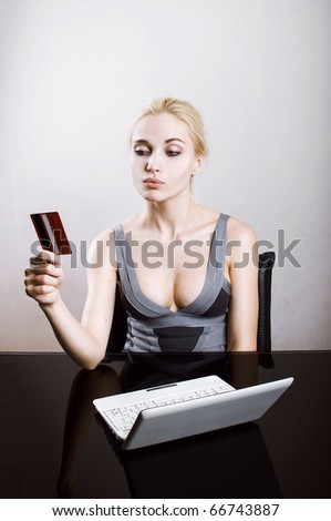 Young woman holding on-line credit card - stock photo