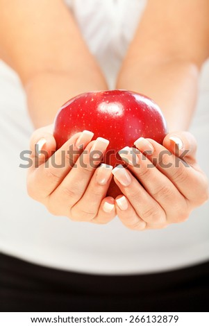 Young woman holding one red apple in her hands, isolated on white - stock photo