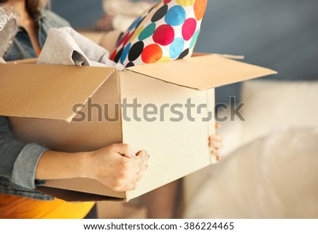 Young woman holding open cardboard box with things for moving into new house - stock photo