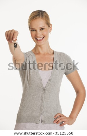 young woman holding out keys towards camera on white seamless background - stock photo