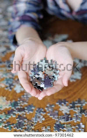Young woman holding pieces of puzzle in her hands - stock photo