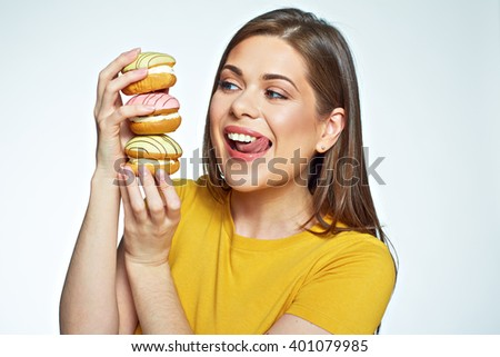 Young woman holding pile cake and licked lips by looking at them. Isolated close up face portrait. - stock photo