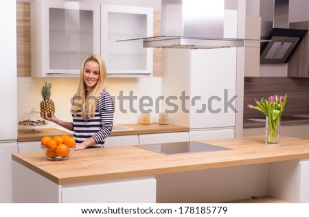 Young woman holding pineapple in modern kitchen - stock photo