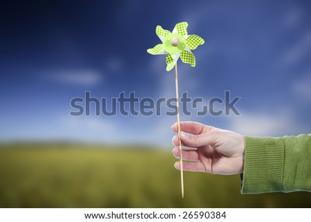 Young woman holding pinwheel windmill outdoors - spring concept - stock photo