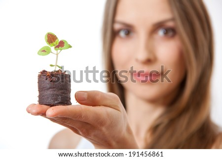 young woman holding plant, coleus sprout. Isolated on white background