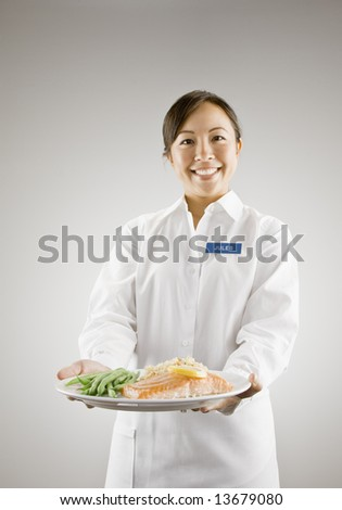 Young woman holding plate of salmon and vegetables - stock photo