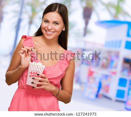 Young Woman Holding Popcorn Packet, outdoor - stock photo