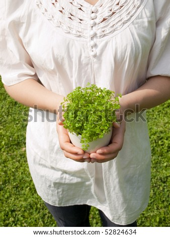 Young woman holding potted plant