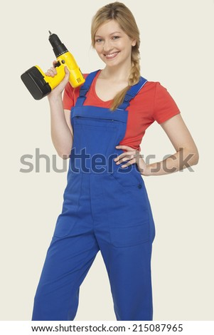 Young woman holding power drill smiling - stock photo