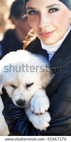 Young woman holding puppy - stock photo