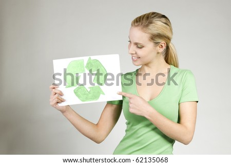 Young woman holding recycling symbol