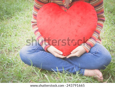 young woman holding red heart, retro style - stock photo