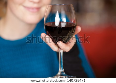 Young woman holding red wine glass at restaurant - stock photo