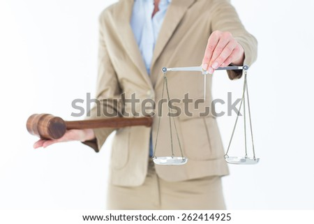 Young woman holding scales of justice and a gavel on white background - stock photo