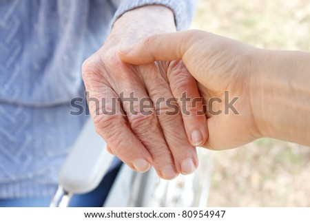 Young woman holding senior woman's hand - stock photo