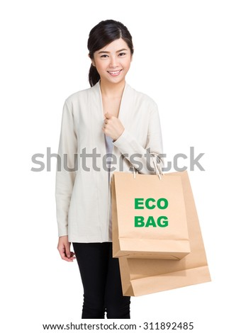 Young woman holding shopping bag and showing eco bag