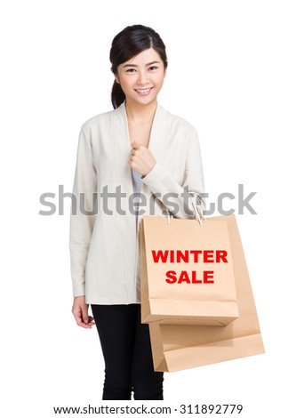 Young woman holding shopping bag and showing winter sale
