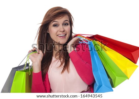 Young woman holding shopping bags and smiling