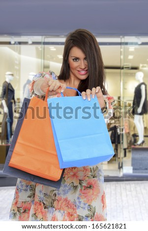 young woman holding shopping bags in front of the store - stock photo