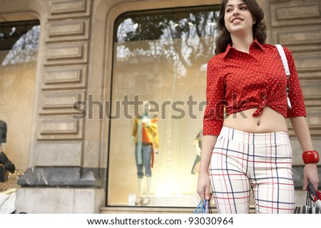 Young woman holding shopping bags, standing by shop window.