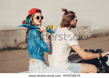 Young woman holding skateboard. Young guy and girl riding on a sunny day