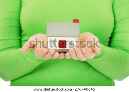 Young woman holding small house. - stock photo