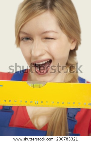 Young woman holding spirit level winking - stock photo