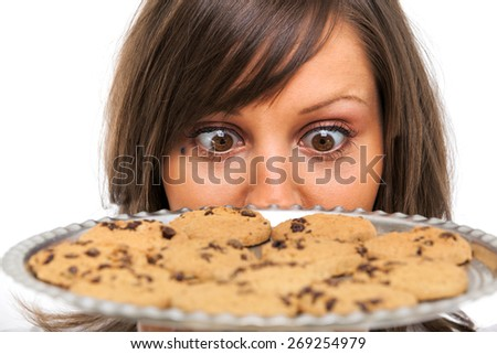 Young woman holding staring at a tray with homemade chocolate cookies - stock photo
